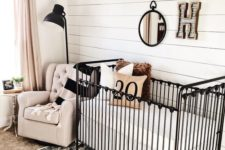 a farmhouse nursery with a white plank wall, a printed rug, a black metal crib and some more black touches for drama