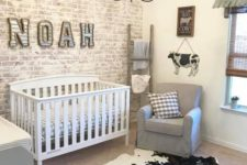 a farmhouse nursery with a whitewashed brick wall, vintage furniture, funny cow signs and a cowhide rug on the floor