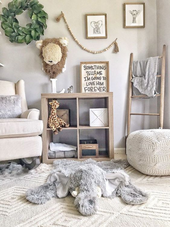 a farmhouse nursery with knit and faux fur items, wooden items, a wood bead garland, a leaf wreath on the wall