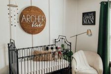 a nursery with a cool farmhouse-style wooden sign