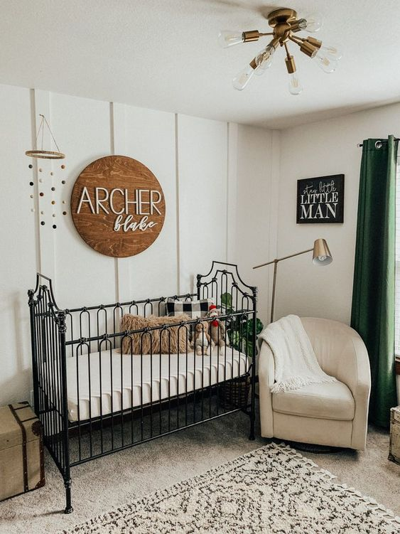 a farmhouse nursery with white walls, a black vintage bed, a wooden sign, gold and brass touches for more chic