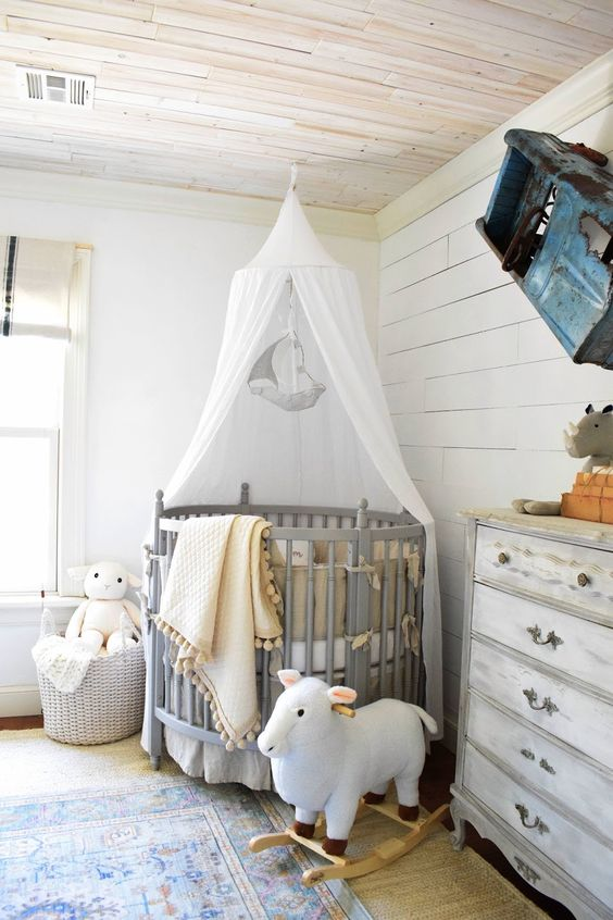 a farmhouse nursery with whitewashed grey furniture, a crib with a canopy, a vintage car on the wall and cute toys