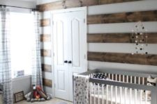 a farmhouse woodland nursery with a striped wall, a grey crib, a carpet on the floor, striped curtains and grey furniture