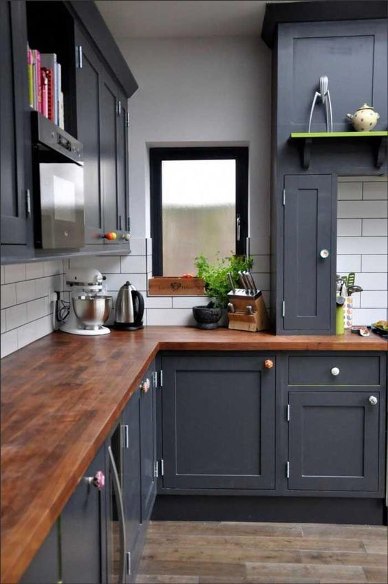 a graphite grey kitchen with a dark stained butcher block countertop that enriches the look of the space