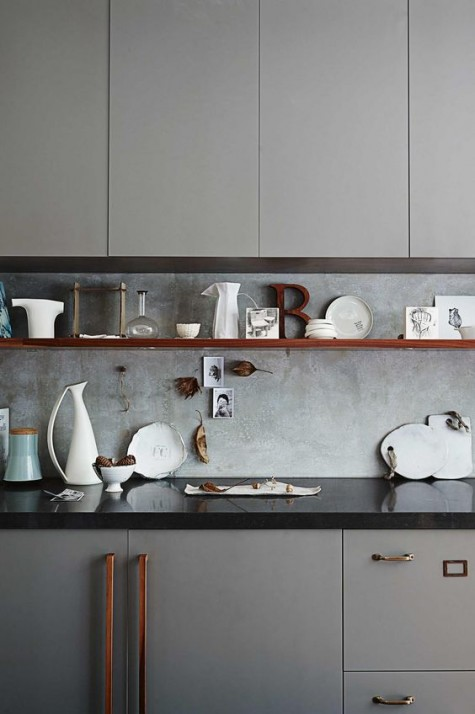a grey kitchen with a black countertop and a concrete backsplash for a textural look
