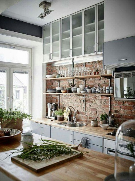 a grey kitchen with an industrial feel and light colored butcher block to make it look more natural