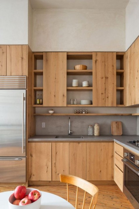 a light-colored wooden kitchen is made more modern with concrete countertops and a backsplash