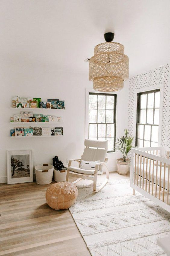 a minimal boho nursery with a printed wall, a wicker lamp, a leather ottoman and a comfy Poang chair by IKEA