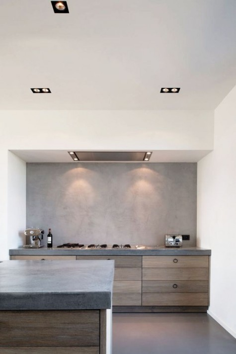 a minimalist and industrial kitchen with a concrete backsplash and countertops plus wood for a texture