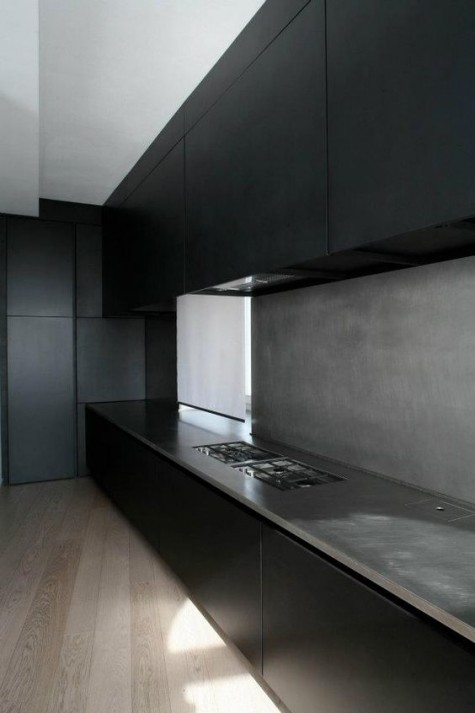a minimalist black kitchen with a concrete backsplash and countertops for more interest