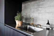 a minimalist dark kitchen with a raw concrete backsplash and a metal countertop that adds texture