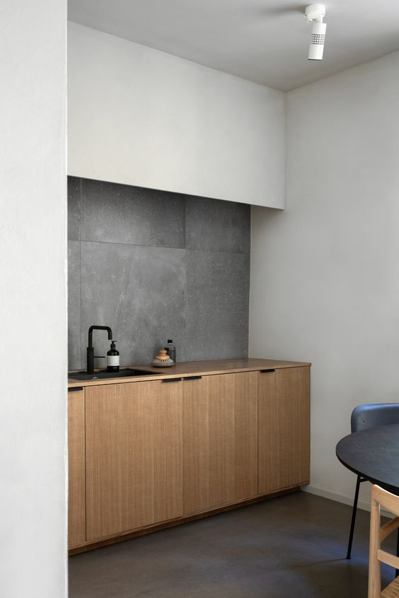 a minimalist kitchen corner with white and wooden cabinets and a concete tile backsplash to highlight the style