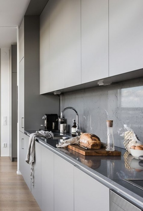 a minimalist light grey kitchen with a concrete backsplash and a glass cover to avoid splashes