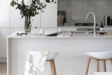 a minimalist white kitchen with a concrete backsplash that adds texture to the space and a sleek stone countertop