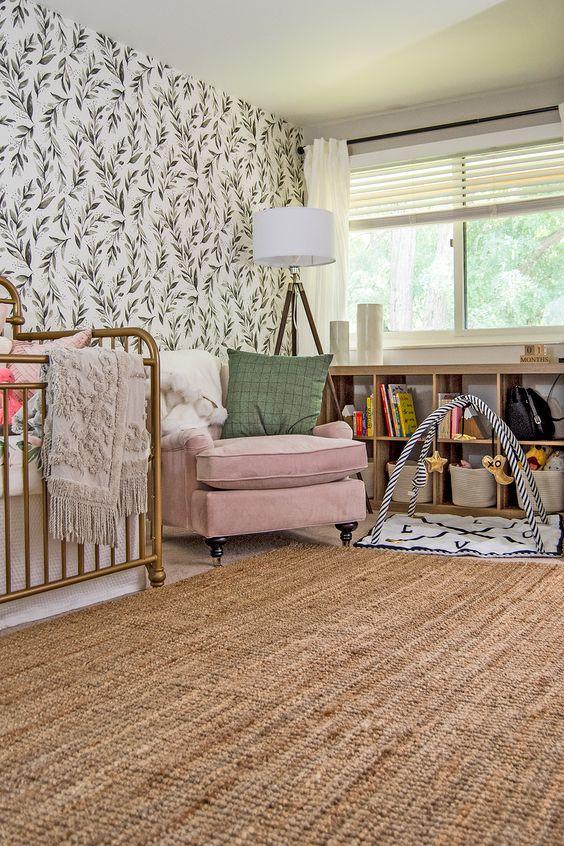 a modern farmhouse nursery with a botanical wall, a jute rug, a brass bed, a pink chair and bookshelf under the windowsill