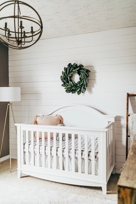 a modern farmhouse nursery with a white plank wall, a vintage crib and chandelier, a leaf wreath and a floor lamp