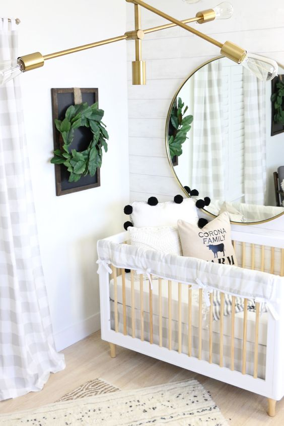 a modern farmhouse nursery with white plank walls, a neutral wooden crib, a gold chandelier and a greenery wreath