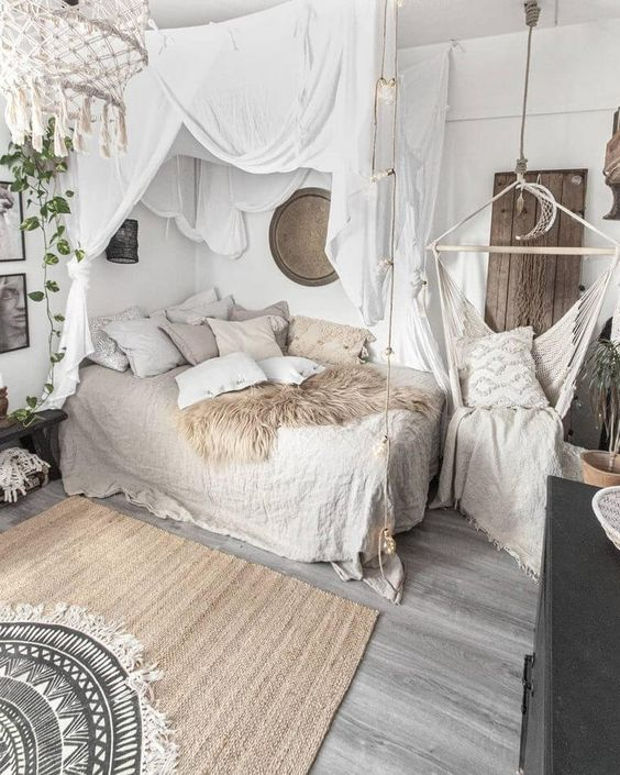 a neutral boho bedorom with a bed with lots of pillows and linen bedding, a canopy, a hanging chair, a woven tassel chandelier and layered rugs