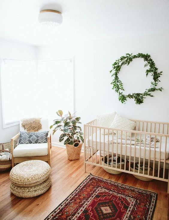 a neutral boho nursery with a greenery wreath, a bright rug, jute ottomans, printed pillows and a potted plant
