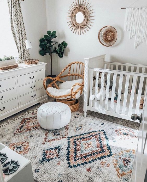 a neutral boho nursery with a printed rug, white furniture, a rattan chair, some baskets and wicker trays