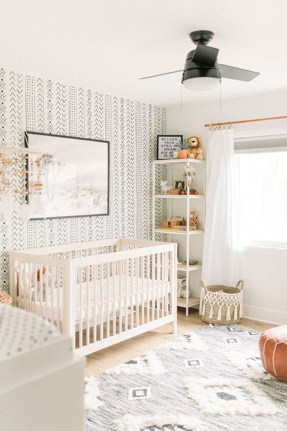 a neutral boho nursery with a printed wall, a printed rug, a leather ottoman, a white crib and a woven basket