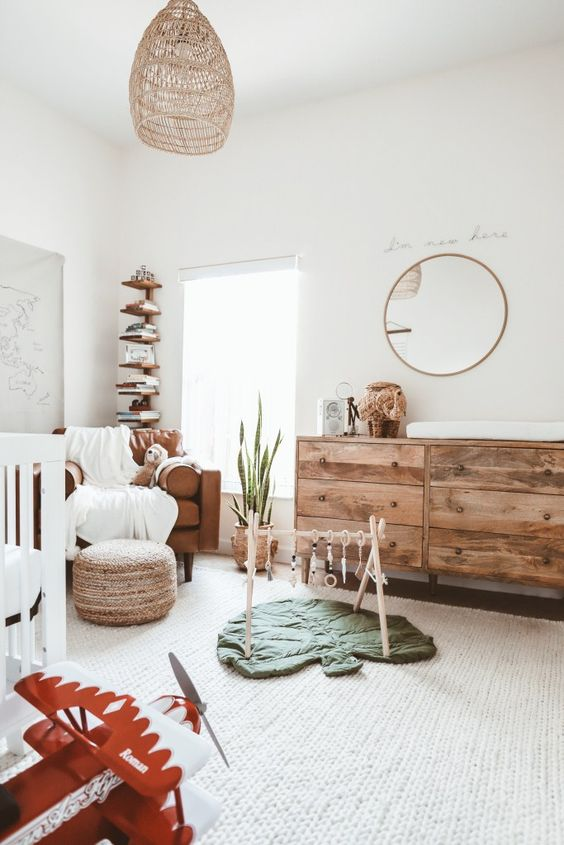 a neutral boho nursery with a rattan lamp, a wooden dresser, layered rugs, a leather chair and a wooden shelf in the corner