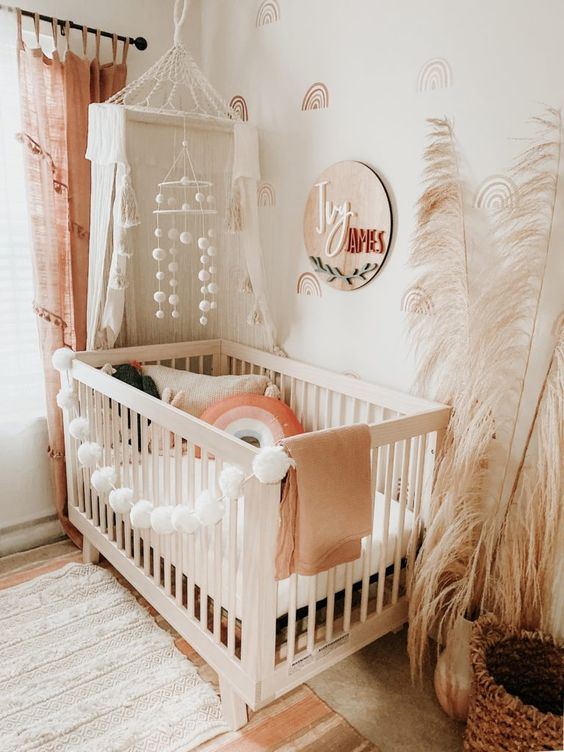 a neutral boho nursery with a white crib, pink curtains, a wooden sign, pompom decor and pampas grass