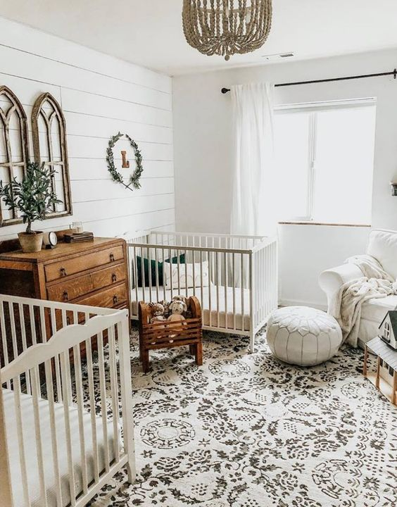 a neutral farmhouse nursery with a printed rug, white beds, a white leather ottoman, stained wooden furniture and a beaded chandelier
