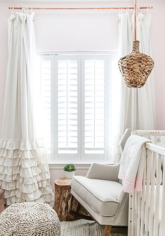 a neutral farmhouse nursery with a vintage feel, a ruffle curtain, knit items, a rattan lamp and a large crib
