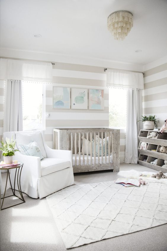 a neutral farmhouse nursery with striped walls, a wooden furniture, a watercolor gallery wall and potted greenery
