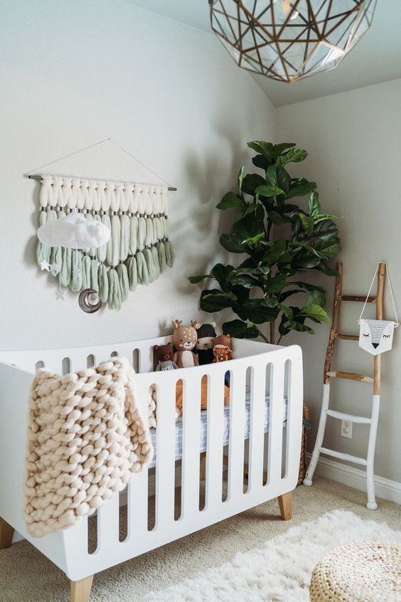 a nueautrla boho nursery with a large modern crib, a macrame hanging, a potted tree, a geometric 3D lamp and a ladder