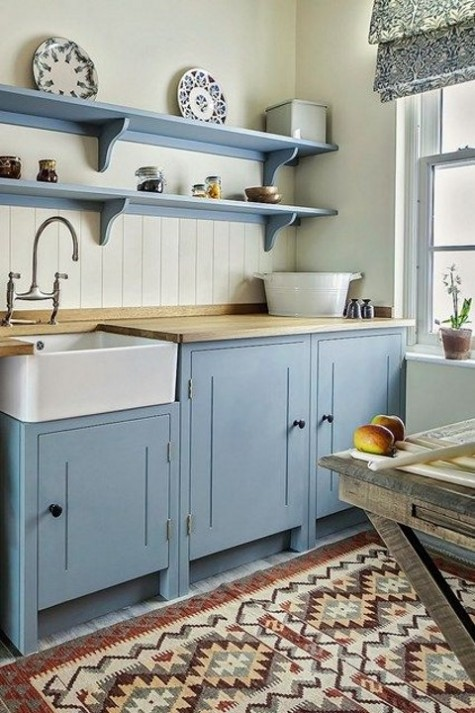 a spatel blue kitchen with light-colored butcher block countertops that add a natural touch to the space