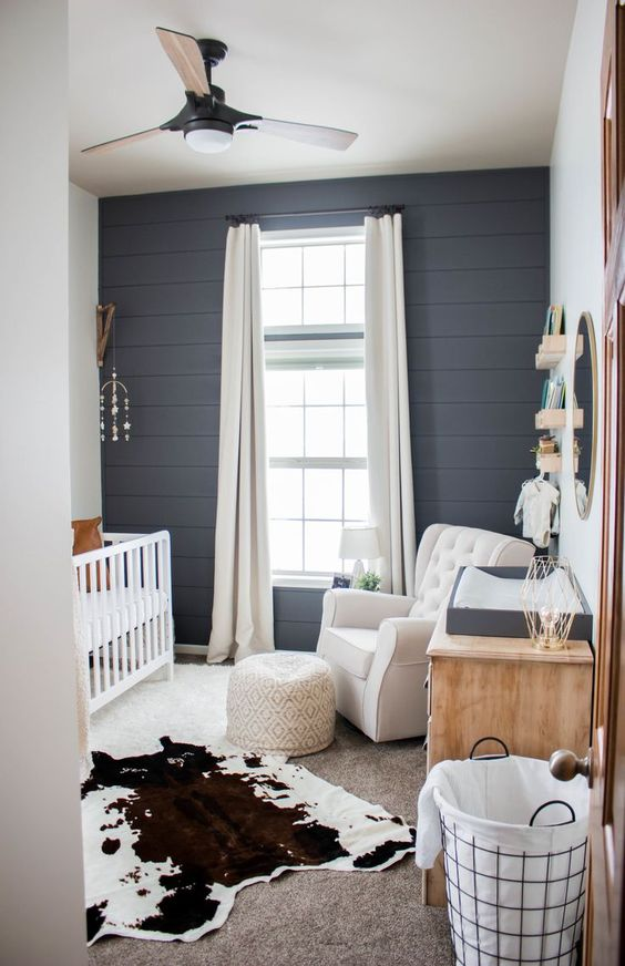 a stylish farmhouse nursery with a grey plank wall, white furniture, layered rugs and a large window for more light