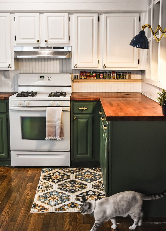 a two tone kitchen in green and white and stained butcher block countertops for a touch of warm color
