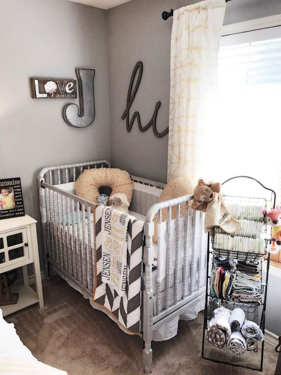 a vintage farmhouse nursery with a white crib, a metal shelf, a pretty gallery wall and textiles to cozy it up