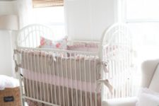 a vintage farmhouse nursery with white walls, woven shades, baskets, a white vintage crib with ruffles and bows