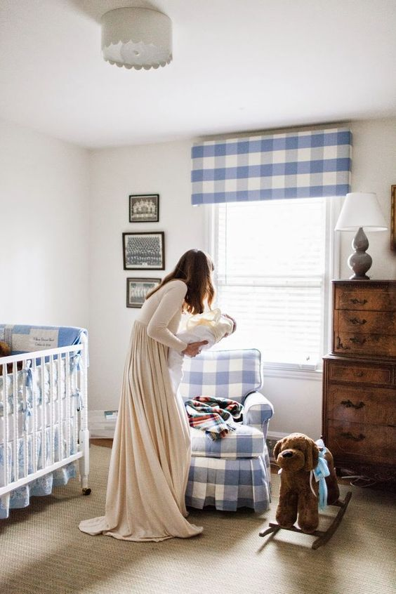 a welcoming farmhouse nursery done with blue and white plaid tetiles, vintage furniture and a gallery wall is cool