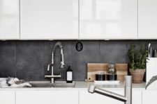 a white contemporary kitchen with a concrete tile backsplash and a matching tabletop of black concrete