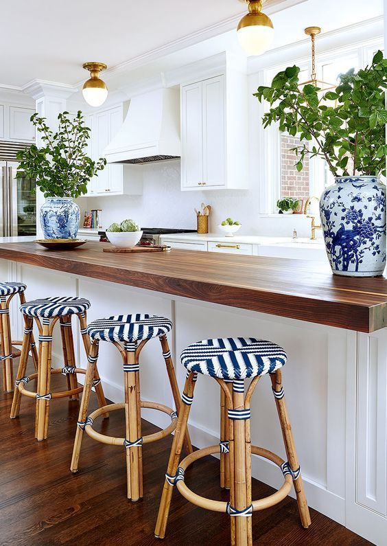 a white kitchen with gold and brass touches and a large kitchen island with a warm-colored butcher block countertop
