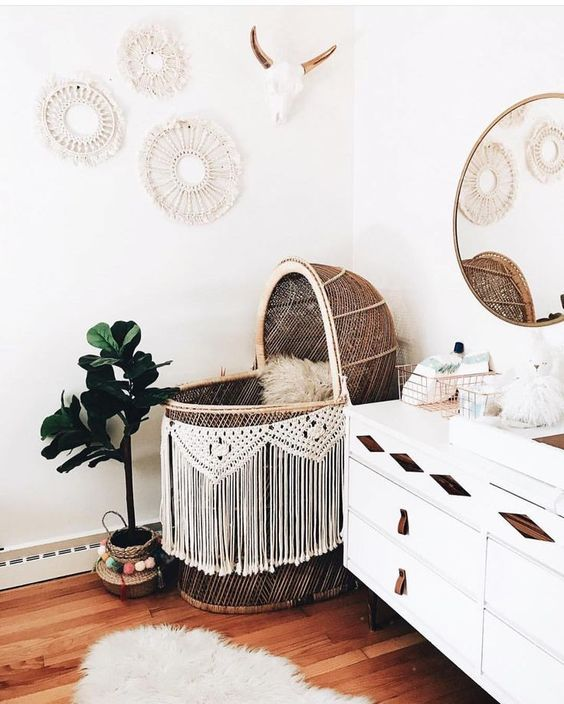 a wild boho nursery with a wicker bassinet and a macrame garland, a white dresser with wooden inserts and leather pulls, a macrame gallery wall and potted greener