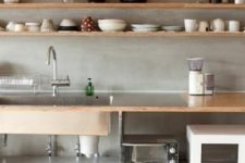an airy modern kitchen with plywood shelves and a countertop and a concrete backsplash