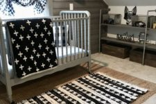 an attic farmhouse nursery with a wooden accent wall, layered rugs, printed textiles and a metal shelving unit