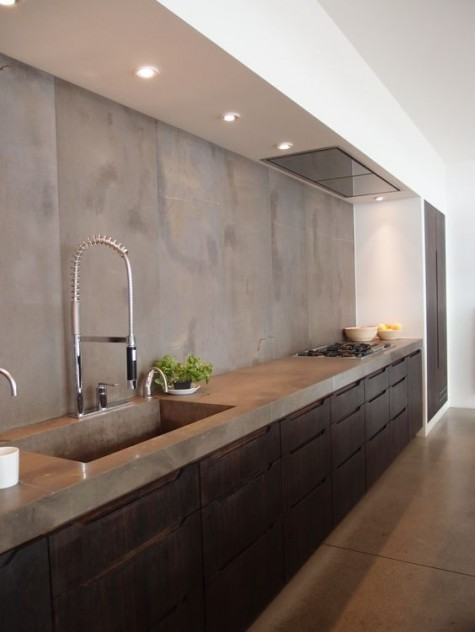 an industrial dark metal kitchen with a concrete countertop plus sink and backsplash