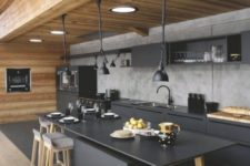 an ultra contemporary kitchen with matte black cabinets and a kitchen island plus a concrete backsplash
