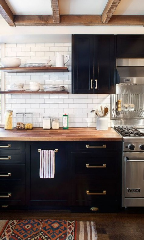 black cabinets with brass handles look great with butcher block countertops that soften the space