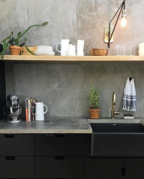 black industrial cabinets, wooden shelves that contrast and a concrete backsplash and countertops