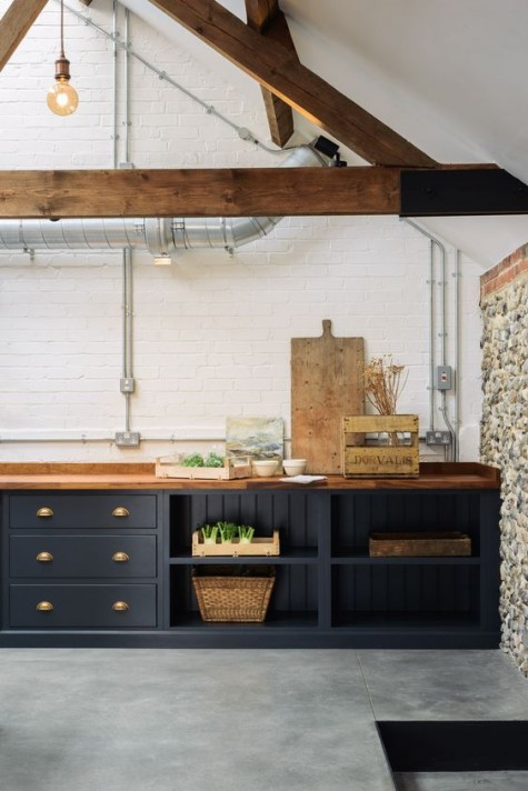 graphite grey cabinets and rich-colored butcher block countertops plus matching wooden beams