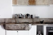 masonry and a concrete backsplash and countertops echo and make the all-white space softer and cozier