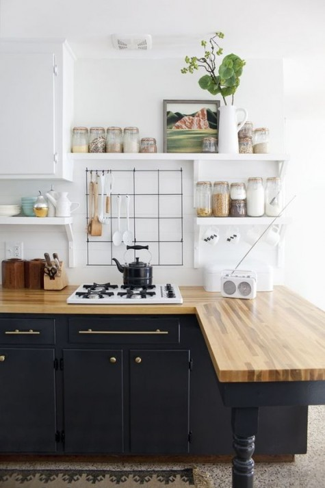 retro-inspired black cabinets with light-colored butcher block countertops that soften the monochromatic kitchen