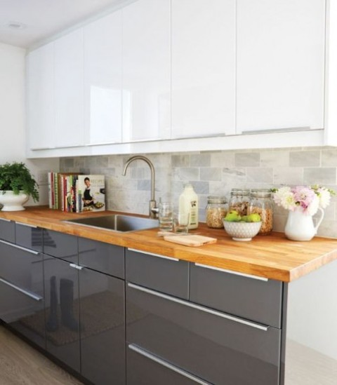 sleek white and grey kitchen with light-colored butcher block countertops for a softer look
